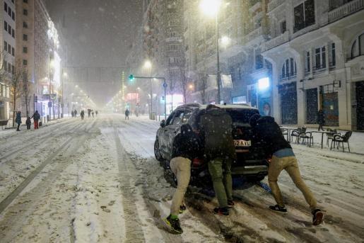 Varias personas empujan un coche en la Gran Vía, en Madrid, en una jornada en la que la Agencia Estatal de Meteorología (Aemet) ha activado el nivel rojo por la previsión de fuertes nevadas.
