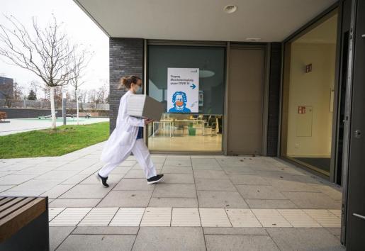 Una trabajadora sanitaria transporta una caja con vacunas contra el coronavirus en Alemania.