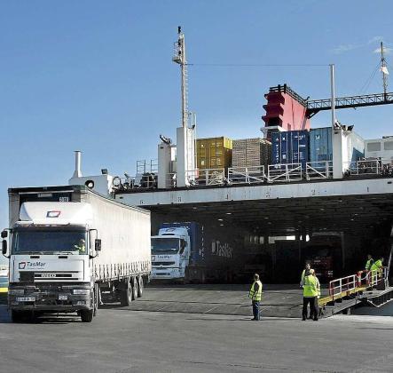 Imagen de archivo de camiones descargando mercancías de un barco en el puerto de Ibiza.