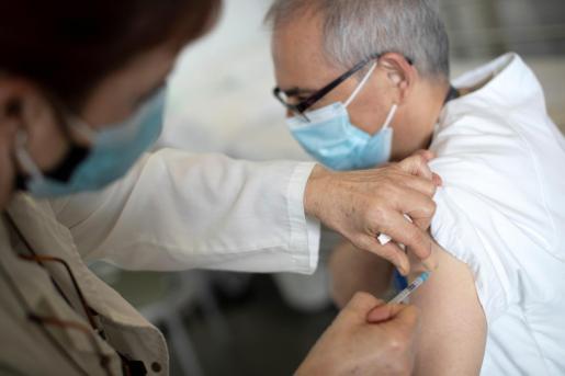 Una enfermera inyecta la vacuna de COVID-19 a un compañero.
