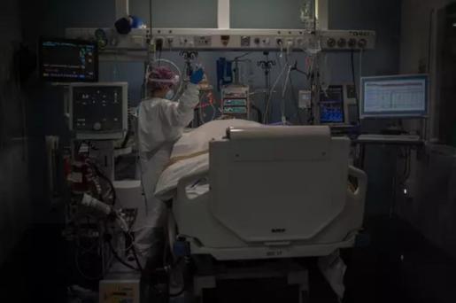Trabajadores sanitarios protegidos atienden a un paciente en la Unidad de Cuidados Intensivos (Archivo) .