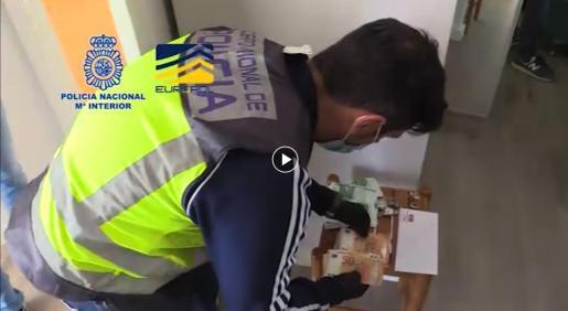 Un agente cuenta el dinero intervenido en una de las casas.