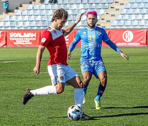 Jaume Villar, centrocampista del CD Ibiza, se prepara para golpear el balón ante la mirada de Vinicius, del Andratx.