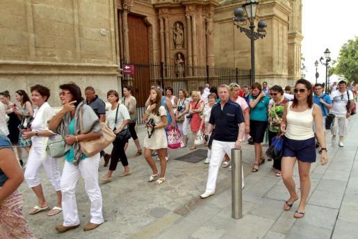 Un grupo de turistas rusos pasean por los aledaños de la Catedral de Palma este verano.