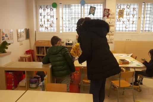 Una profesora atiende con abrigo a un alumno durante la ola de frío.