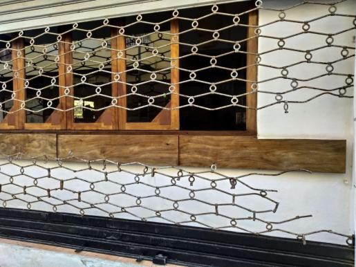 Imagen de la persiana del establecimiento que fue cortada para llevar a cabo el robo.