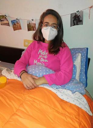 María, en su cama, en una imagen tomada por su pareja (lleva mascarilla porque está aislada en su casa y su pareja le hizo la foto).