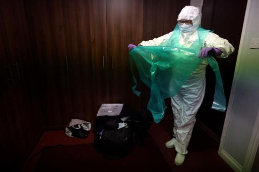 Embalmer Mary Evans dresses in Personal Protective Equipment (PPE) before entering the mortuary at W. Uden & Sons Family Funeral Directors in Bromley, amid the coronavirus disease (COVID-19) pandemic, in south east London, Britain, January 28, 2021. Picture taken January 28, 2021. REUTERS/Hannah McKay HEALTH-CORONAVIRUS/BRITAIN-FUNERAL