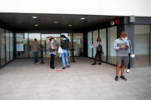 Varias personas esperan a la puerta del SOIB de Ibiza.