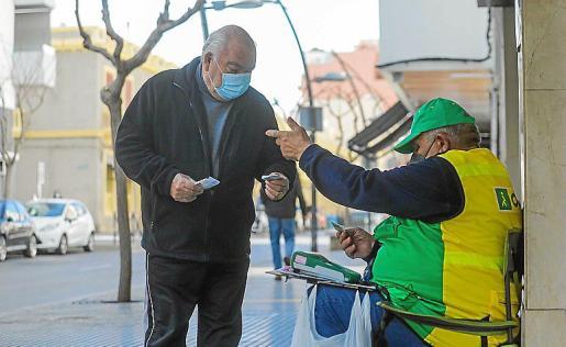 Tomás Ortega vendiendo cupones en la acera de la Avda España.