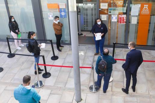 Una empleada del Ayunta miento de Eivissa ofrece información a los ciudadanos que esperan su turno ante las oficinas municipales.