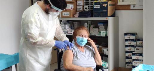 Un enfermero suministra la vacuna de la COVID-19 a una gran dependiente.