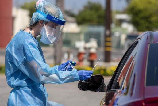 Una sanitaria realiza un test a un paciente en su coche.