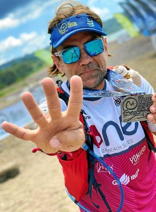 Eusebio Noguera exhibe su medalla de 'finisher' al tiempo que indica con la mano su número de participaciones en Costa Rica.