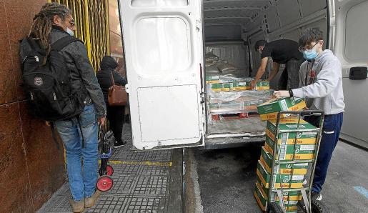 Un voluntario de Cáritas y un trabajador del DC10 descargan la comida ante la mirada de varios usuarios.