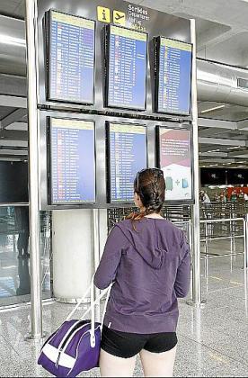 Una joven mira el panel de salidas en el aeropuerto de Palma en una imagen de archivo.