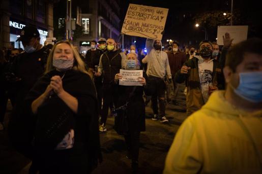 Un grupo de personas participan en una concentración de trabajadores del sector hostelero y el ocio nocturno contra las restricciones aplicadas a causa del Covid-19, en la plaza Urquinaona, Barcelona.