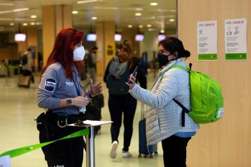 Una pasajera muestra el justificante de viaje en el aeropuerto de Ibiza.