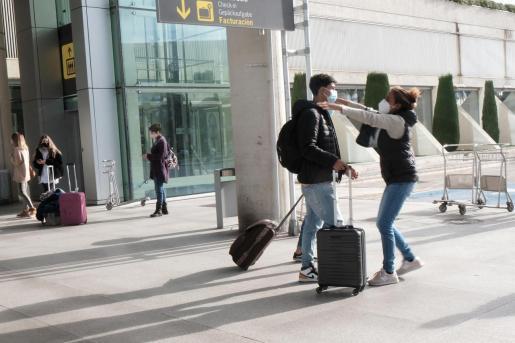 Dos personas se abrazan a las afueras del aeropuerto de Palma, días antes de Navidad, cuando comenzó a aplicarse la obligación de presentar PCR negativa para entrar en Baleares desde la Península.