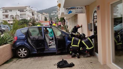 Los bomberos durante la operación para desencajar el vehículo siniestrado.