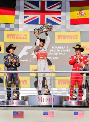 El piloto británico Lewis Hamilton (c) celebra su victoria en el Gran Premio de Estados Unidos junto al segundo clasificado, el alemán Sebastian Vettel (i), y el tercer clasificado, Fernando Alonso (d).