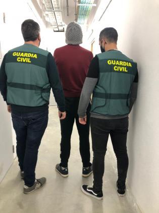 Dos guardias civiles custodian al peligroso delincuente camino de los juzgados.