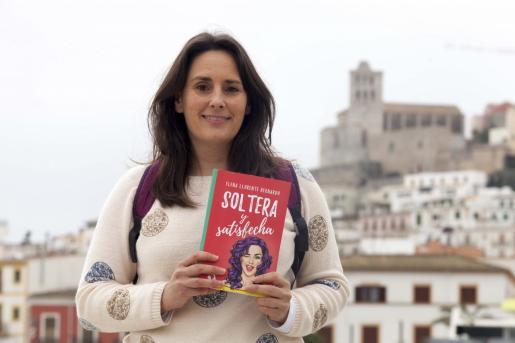 La escritora y profesora ibicenca Elena Llorente posa con un ejemplar de su exitosa novela 'Soltera y satisfecha' con el paisaje de Dalt Vila de fondo. A la derecha la portada del primer libro. El segundo verá la luz entre mayo y junio.