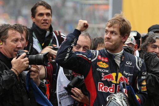 El piloto alemán Sebastian Vettel (d), de Red Bull, celebra la consecución de su tercer título de campeón mundial de Fórmula Uno.