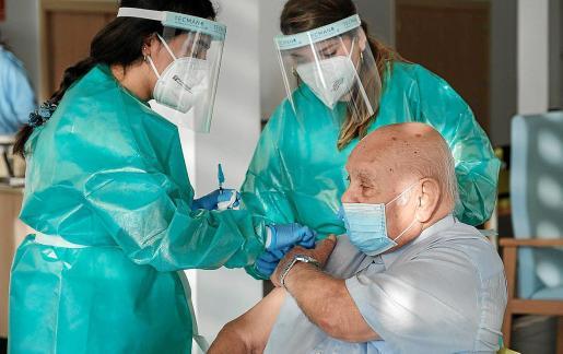 Dos enfermeras ponen la vacuna a un usuario de una residencia.