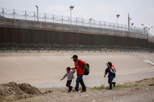 Migrantes antes de cruzar el río Bravo para entregarse a los agentes de la Patrulla Fronteriza de Estados Unidos para solicitar asilo en El Paso, Texas, Estados Unidos.