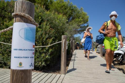 Imagen de archivo de ciudadanos, con mascarilla, de camino a la playa.