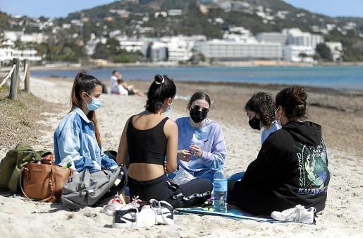 Un grupo de jóvenes, con mascarilla, disfruta del día en la playa.