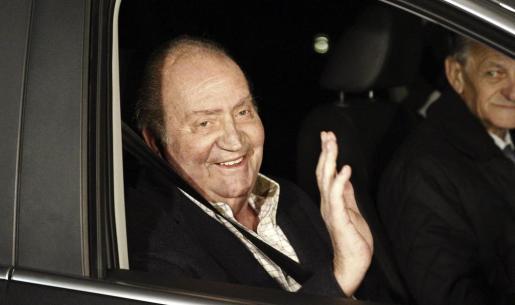 El rey don Juan Carlos saluda al abandonar esta tarde en un automóvil el hospital madrileño Quirón San José.