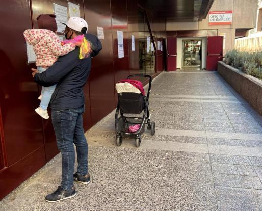Un hombre con una niña pequeña en brazos frente a una oficina de empleo en Madrid.