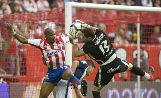 El portero del Tenerife, Sergio Aragoneses, atrapa el balón ante el defensa francés del Sporting de Gijón, Gregory Arnolin, durante el partido, correspondiente a la trigésimo segunda jornada de Liga, que juegan los dos equipos, esta tarde, en el estadio de El Molinón, en Gijón.