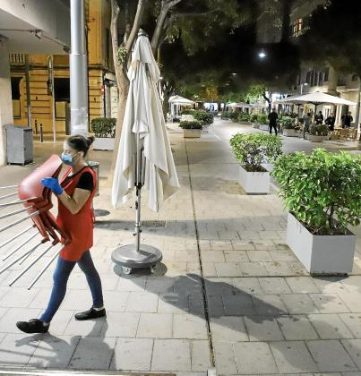 Una camarera recoge las sillas de la terraza al finalizar la jornada. El cierre de la hostelería se mantendrá a las 17.00 horas.