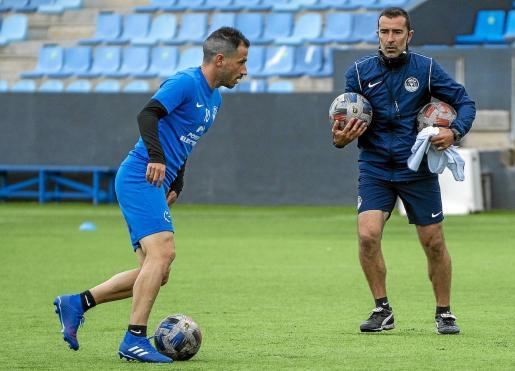 Cirio conduce el balón ante la mirada del técnico Juan Carlos Carcedo en una acción del entrenamiento de ayer de la UD Ibiza.