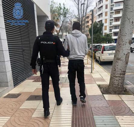 Un agente de la Policía Nacional junto al detenido.