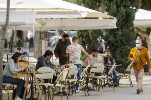Varias personas en la terraza de un bar en el centro de Ibiza.