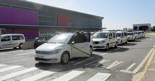 Varios taxis esperando turno en la parada del aeropuerto.