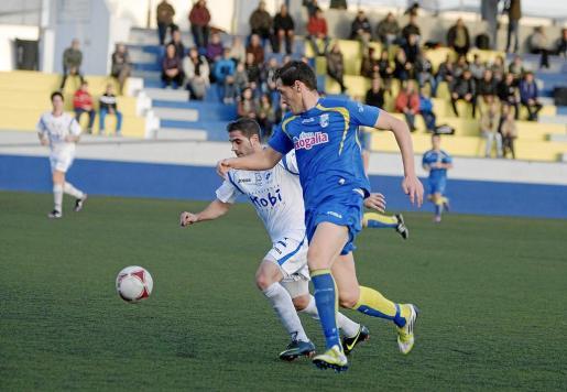 Víctor, defensa del Isleño, pugna por el balón con un jugador del Ciutadella.