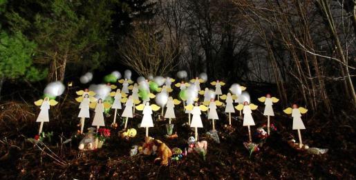 Angelitos de madera pintados de blanco en memoria a las víctimas, como muestra del dolor en un jardín de la ciudad de Newtown.