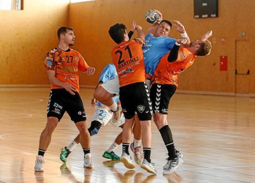 Bernárdez, de la UD Ibiza HC Eivissa, se prepara para ejecutar un disparo ante la oposición de varios jugadores del Torrelavega.
