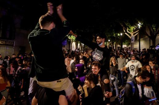 Decenas de jóvenes celebran junto al Passeig de Lluis Companys de Barcelona, el fin del estado de alarma en Cataluña durante la madrugada del domingo, donde los indicadores epidémicos están mejorando gracias a la vacunación masiva de la población.
