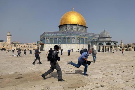 Un miembro de la policía israelí persigue a un hombre con una cámara.