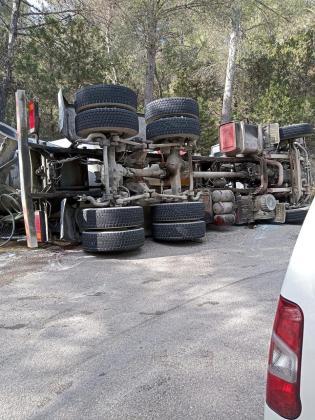 El camión hormigonera volcado en uno de los márgenes de la carretera.