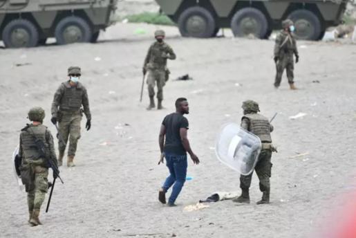 Militares del ejército español efectúan una devolución en caliente a uno de los migrantes que han entrado en Ceuta procedente de Marruecos.