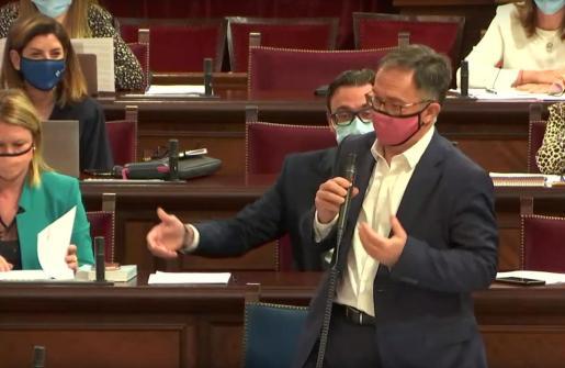 El conseller de Movilidad responde al diputado del PP, Toni Costa, que gesticula detrás de él.