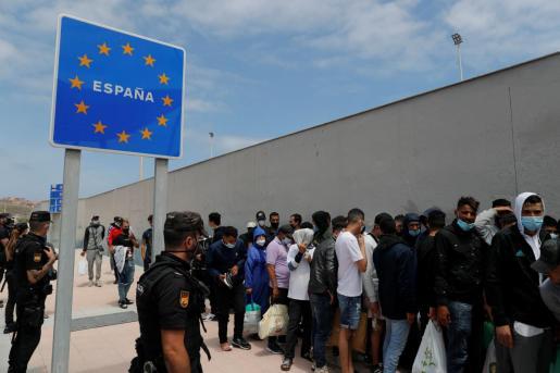 Varios migrantes esperan para pasar la frontera entre Ceuta y Marruecos voluntariamente. La ciudad española de Ceuta, en el norte de África, recupera poco a poco la normalidad tras la llegada masiva de inmigrantes irregulares, muchos de ellos menores.