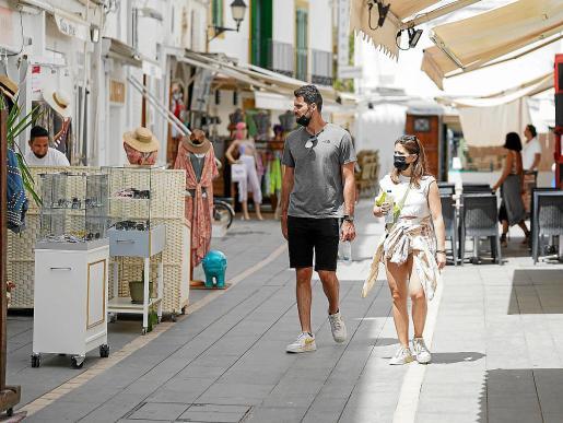 Una pareja de turistas observa las tiendas de una calle del puerto.